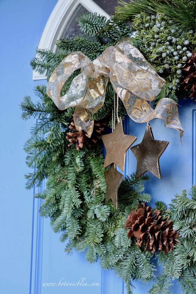 Tips for best ever Christmas wreath on blue front door before replacing brown twine cord with gold cord hangers