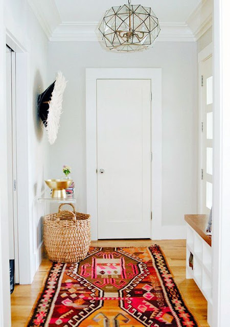 Boho foyer features Greige walls over honey oak hardwood floors layered with a colorful Kilim rug.