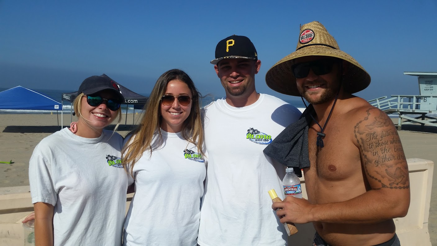Four camp cousnselors and camp directors wearing Aloha Beach Camp shirts standing together at Zuma Beach