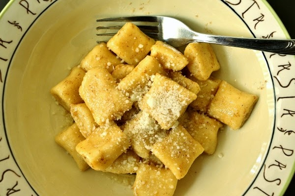 a bowl of gnocchi topped with grated cheese