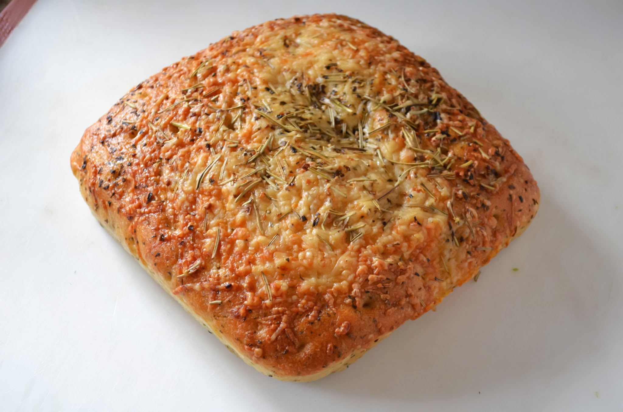 A loaf of focaccia bread on a white cutting board.