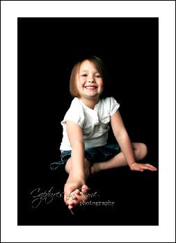 Kansas City Child Photographer girl on black backdrop sitting