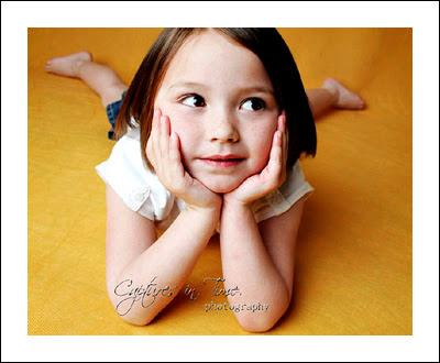 Kansas City Child Photographer girl on yellow backdrop head on hands