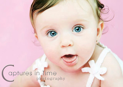 toddler on pink backdrop with tongue hanging out