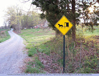 Rural road with horse and buggy hazard sign