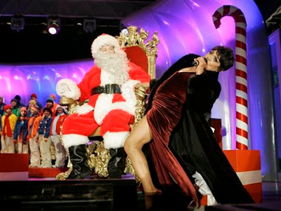 This Dec. 7, 2006 file photo shows Brad Oscar, dressed as Santa Claus, watching Eartha Kitt perform during the Christmas Pageant of Peace Opening Ceremony on the Ellipse in Washington. A family friend says Kitt has died Thursday, Dec. 25, 2008 of colon cancer. She was 81. (AP Photo/Gerald Herbert, file)