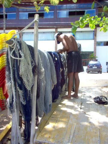 Pescador consertando rede