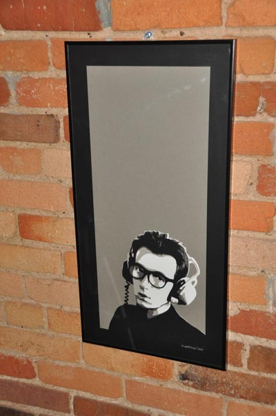 black and white papercut portrait of elvis costello hanging on brick wall