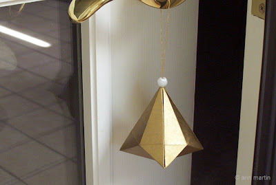 Folded Paper German Bell Ornament hanging on door handle