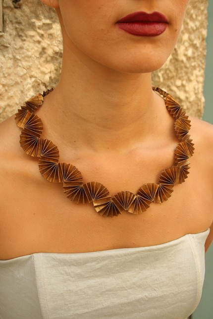 folded gold metallic paper art necklace on model