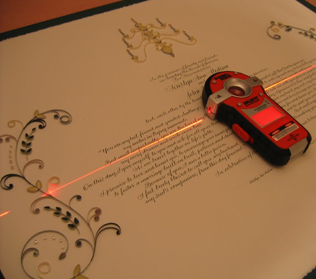 Quilled marriage certificate with laser light for leveling