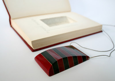 black and red striped book page necklace pendant on black cord with accompanying book from which the layers were cut