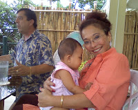 Diana Limjoco holding Alysha with Dave Dewbre in the background.