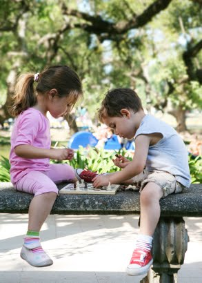 NAMC summer vacation ideas for Montessori families children play chess in garden