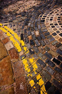 picture of cobbles and yellow lines in a spiral