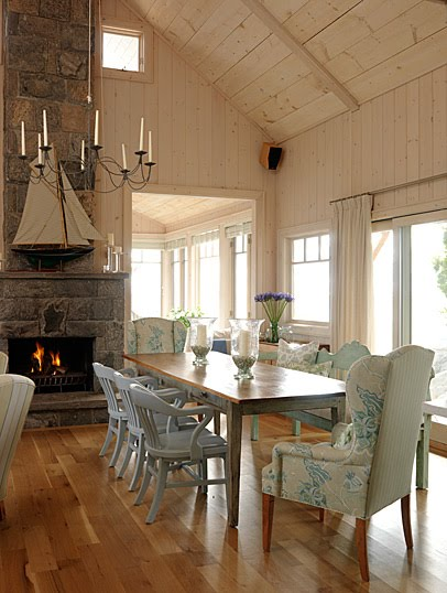Charming dining area with wing chairs, farm table, and stone fireplace