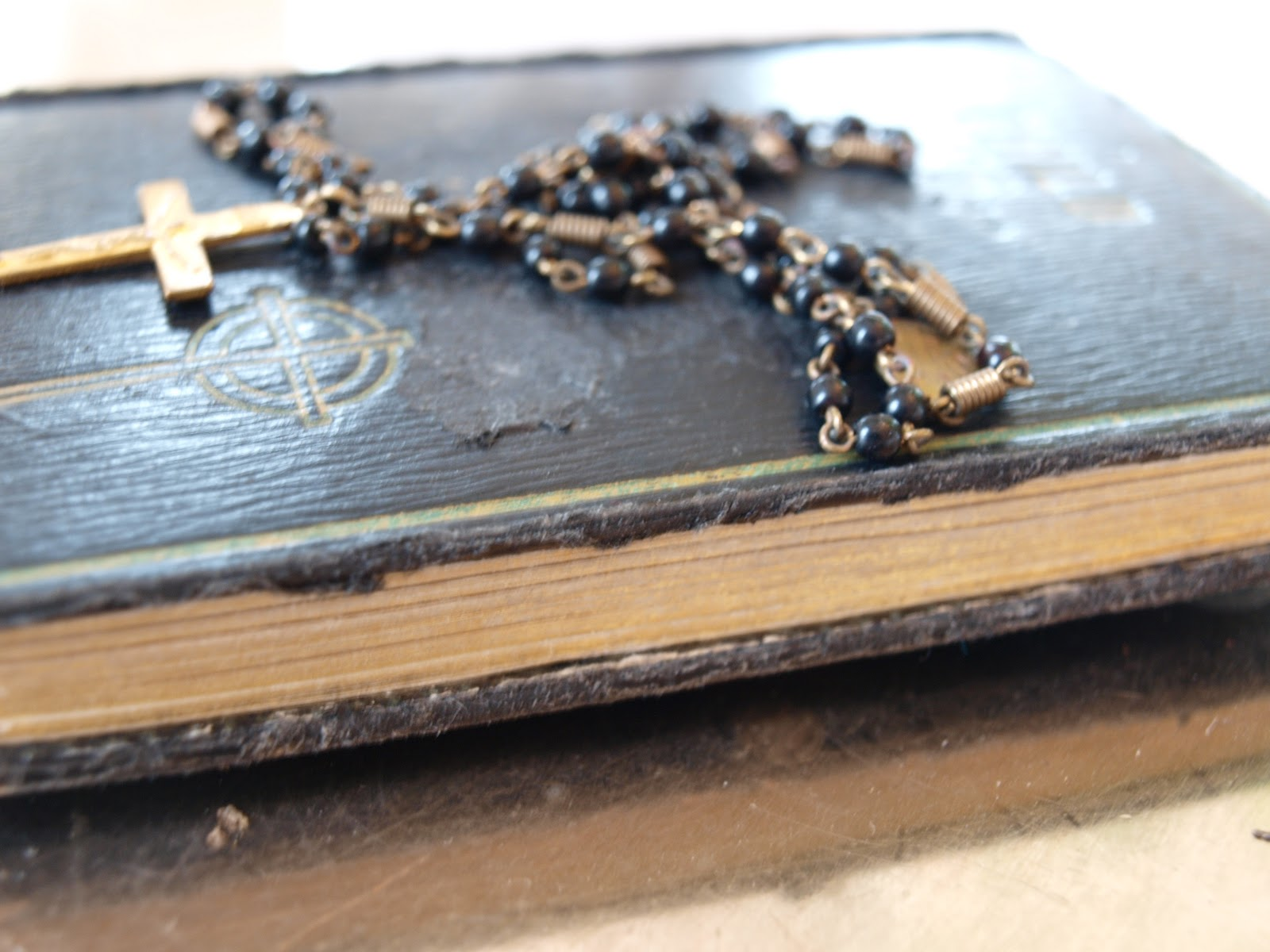 Vintage bible with rosary necklace on top
