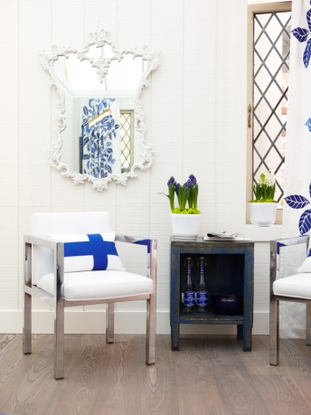 Modern chairs with blue cross on cushion and shiplap walls in modern farmhouse design by Sarah Richardson