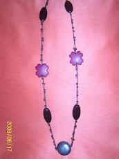 Collar largo en tonos lila, negro y azúl, en madera