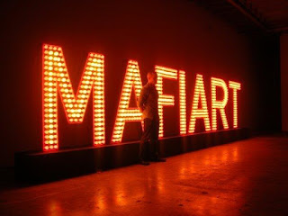 Klaus Guingand artwork: MAFIART - Wooden and aluminum letters, red and yellow light bulbs, 26 feet x 1,47 feet x 7,22 feet