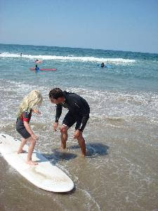 Aloha Beach Camp Keiki Camp Director Scott Kelly teaches camper Sophie, age 5, how to surf at Zuma Beach