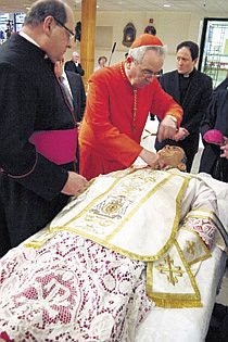 'Monsignor George Tomichek (left) who has been at each opening of St. John Neumann's casket since 1962, watches Justin, Cardinal Rigali adjusting the saint's new vestments. Monsignor John McIntyre (right) along with Auxiliary Bishop Joseph Cistone, Fathers Kevin Moley & Patrick Woods, and Monsignor Daniel Sullivan (not pictured) also attended the solemn and moving event.'