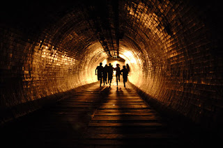 People in a tunnel, running.