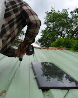 Fabrice drilling holes for the solar panels