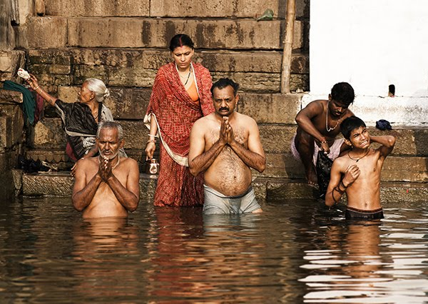 indians praying on bathing ghats in varanasi