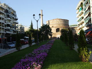 more Thessaloniki, normal homes on both sides, beautiful flowers in the middle and ancient ruin a bit higher