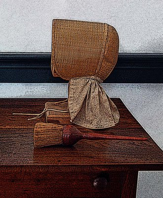 a Shaker bonnet and clothes brush rest on a side table