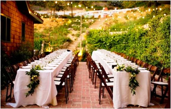 Outdoor wedding reception with Garlands made of California bay leaves, persimmons, raspberry branches and figs by Lily Lodge