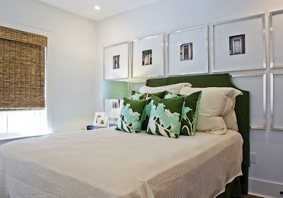 Bedroom in Alys Beach with a green upholstered headboard, green and white floral pillows and silver square frames with black and white photos