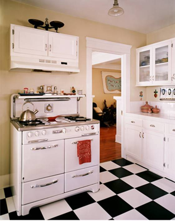 Kitchen with a vintage stove, black and white checkerboard tile floor, pale yellow walls, white cabinets and drawers and white upper cabinets with glass fronts