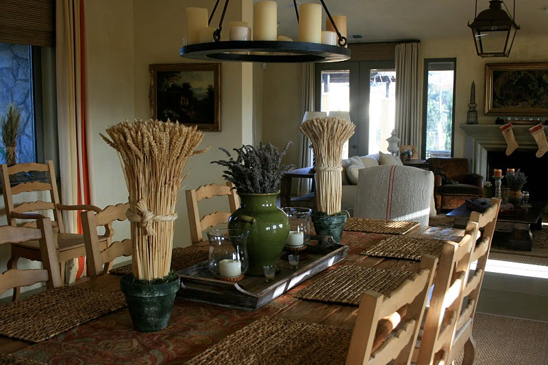 Dining room in Delores Arabian's Sonoma County home with a farmhouse style table, vintage grain sack upholstered host chairs and wheat topiaries
