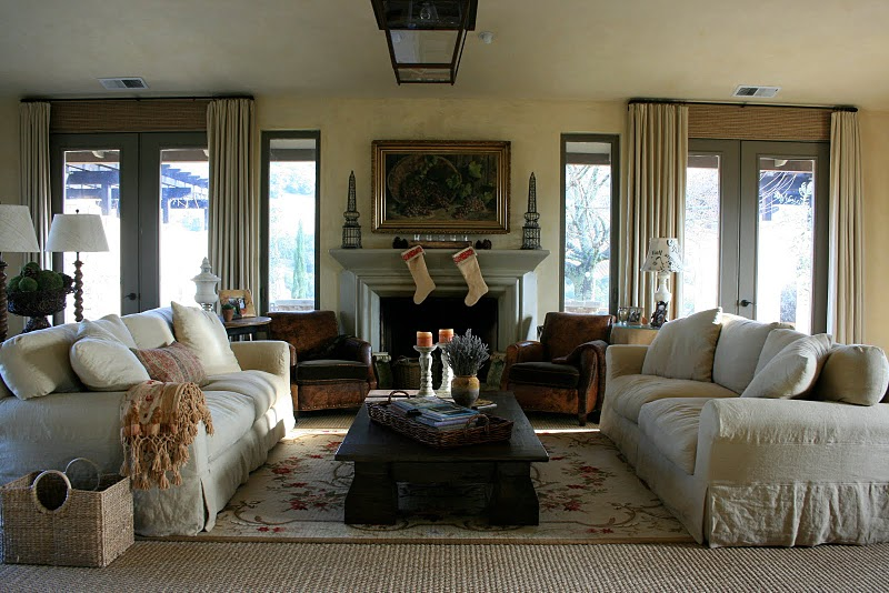 Delores Arabian's rustic living room in her Sonoma County home with dueling oversized slipcovered sofas, leather club chairs and a traditional fireplace