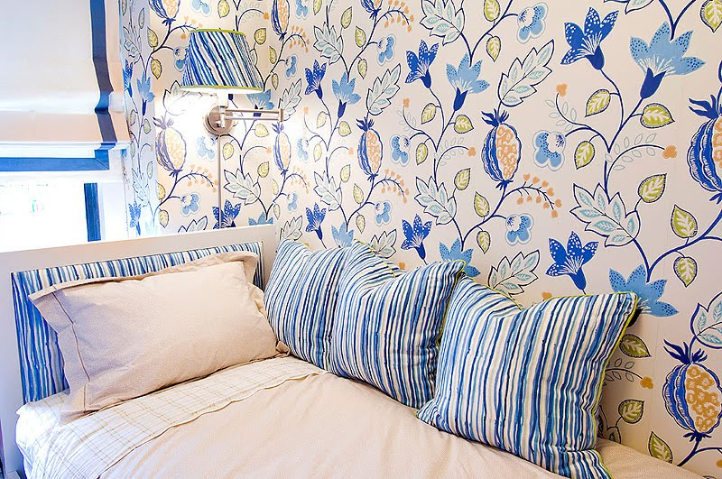 Guest bedroom with colorful floral wallpaper, striped headboard and matching accent pillows