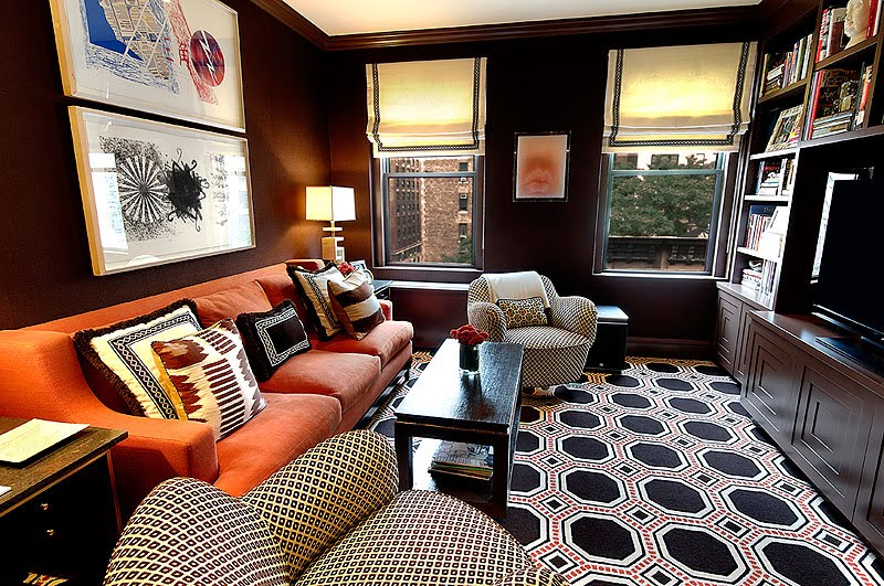 Family room with octagon graphic print rug, orange sofa, built in bookcase and diamond printed club chairs