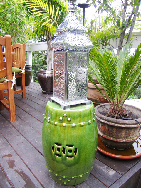 Green ceramic garden stool and a silver lantern on an outdoor deck