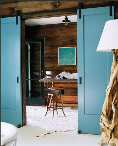 Room with a blue sliding barn door opening to a hallway with a writing desk and wood wall
