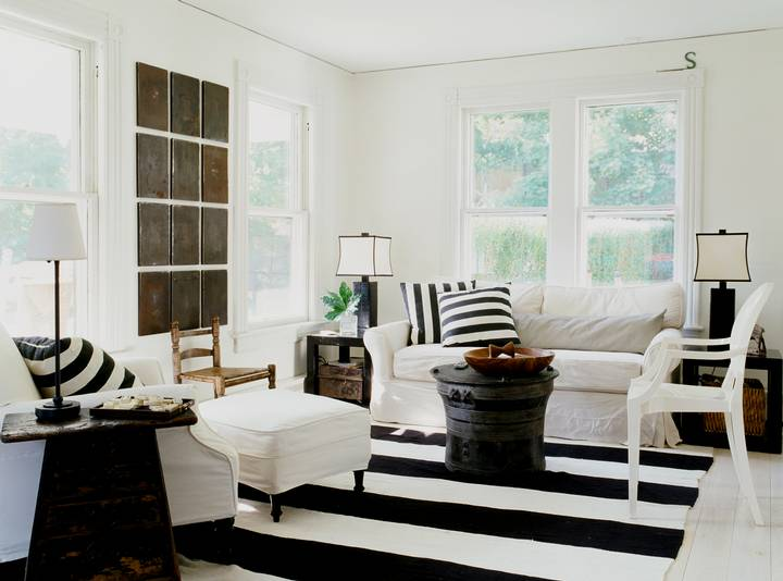 Living room in a cottage with black and white striped rug, white sofa, armchair and ottoman with black and white striped accent pillows and a black coffee table