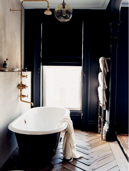 Bathroom with navy walls and a matching stand alone tub, herringbone wood floor, and a door with roman shades for privacy