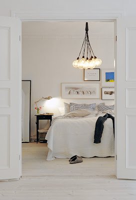 White bedroom with light wood floor, black nightstand with a metal desk lamp, blue accent pillows on the bed and a light bulb chandelier