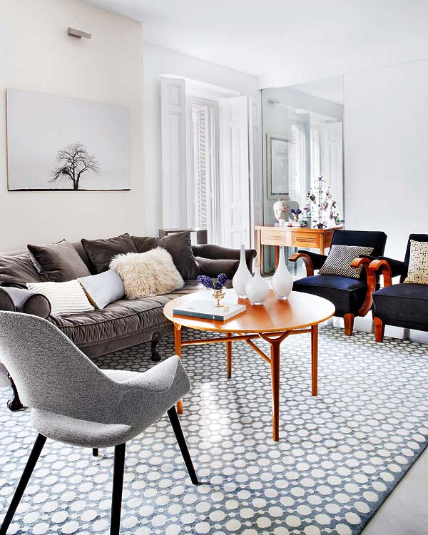 Living room in an apartment with a geometric print rug, dark blue-grey velvet sofa, two blue armchairs, a grey upholstered chair, and a round wood coffee table