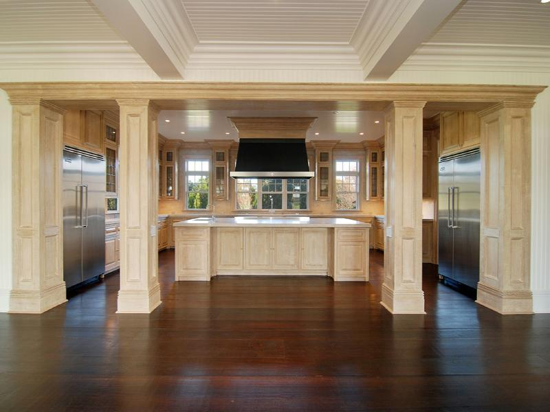 Empty kitchen in a Hampton's farm with coffered ceiling, wood floor, stainless appliances light wood cabinets, drawers and columns and a matching island