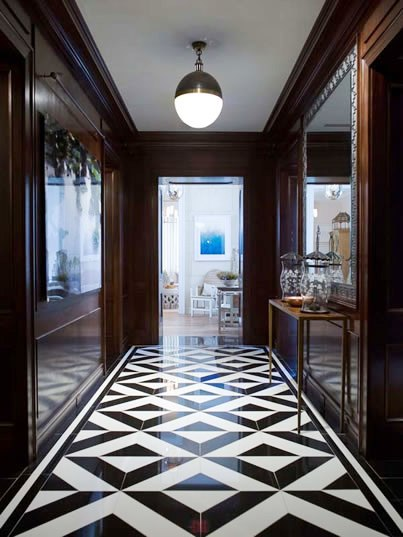 hallway with black and white geometric tiles, large mirrors on each side and a single pendant light