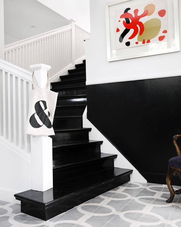 Foyer with a black staircase with white trimming and grey and white cement Moroccan tiles by Popham Designs