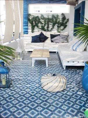 Patio with blue and white cement Moroccan tiles, white outdoor benches with white cushions and blue and white accent pillows