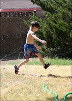 Galen having fun jumping - as usual - through the sprinkler