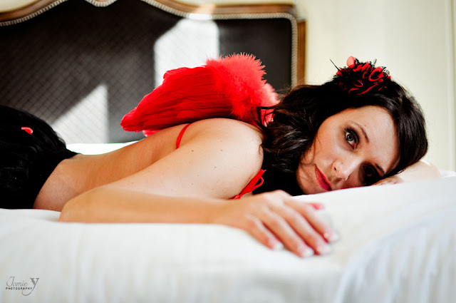 Brunette laying down on bed during boudoir shoot staring at camera at Green Valley Ranch